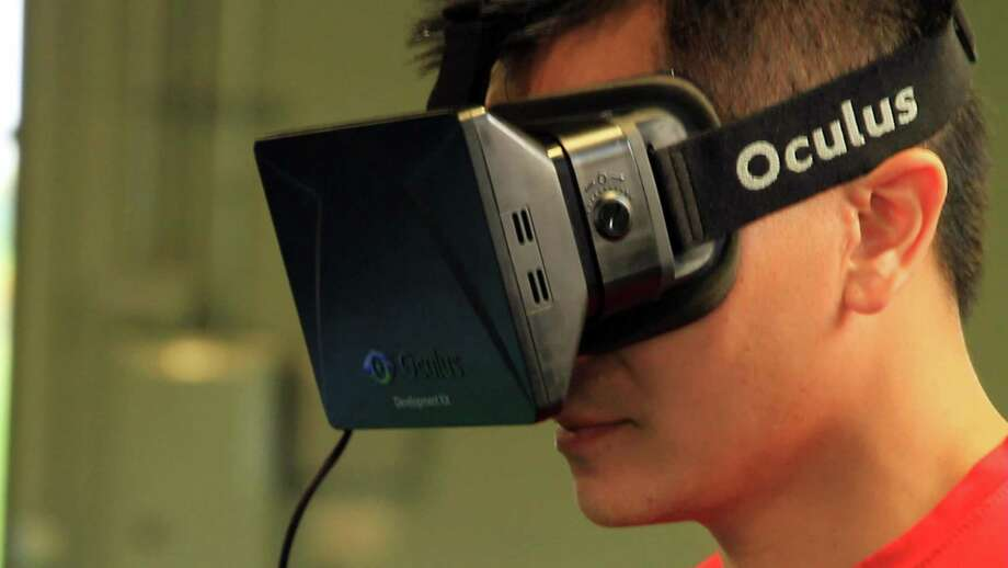 In this Aug. 11, 2014, photo provided by EON Sports VR, sports performance manager and strength and conditioning coach Doran Lovan wears a vitual-reality headset to view a 360-degree virtual simulation, in Overland, Kansas. College football teams have been using virtual reality as a training tool, putting players in an interactive 360-degree environment without having to be on the field. Photo: Brendon Reilly /Associated Press / EON Sports VR