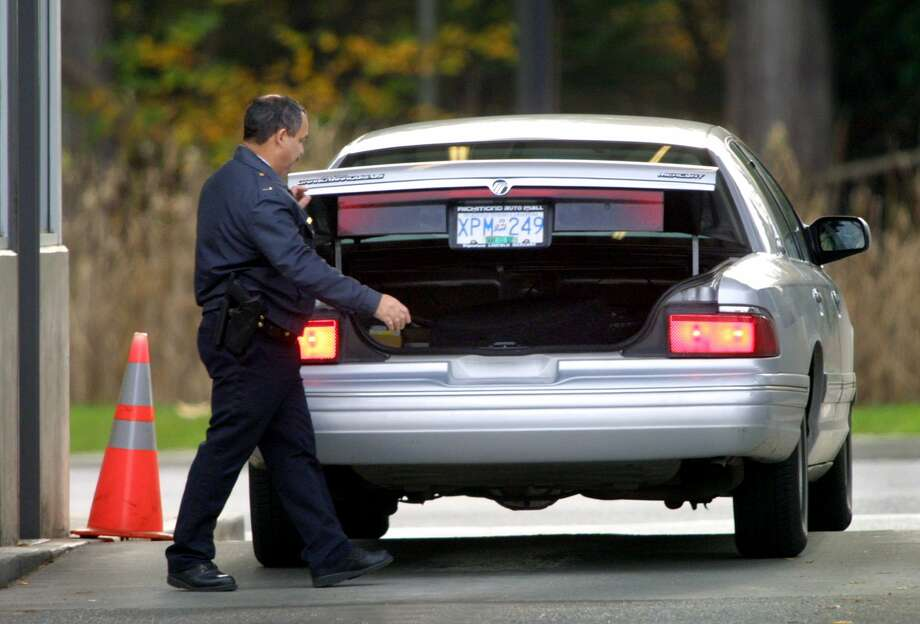 "A United States border guard inspects a vehicle from Washington State at the border crossing between Point Roberts, Washington and British Columbia. Point Roberts can only be reached by car through B.C. ""Nonessential"" travel between U.S. and Canada now banned. Photo: Getty Images"