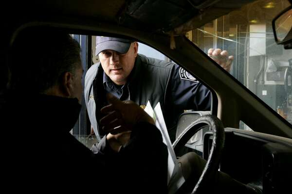 SAN YSIDRO, CA-, JUNE 1: Customs and Border Protection agent Bob Schulze checks an ID from a motorist crossing into the United States from Mexico at the San Ysidro Port of Entry June 1, 2009 in San Ysidro, California. The Western Hemisphere Iniative (WHTI) was put into effect today at all Canadian and Mexican border crossings where visitors and residents must present an approved travel document when entering the U.S. at any land or sea ports of entry. These travel documents include a U.S. passport or passport card, as well as a Trusted Traveler Card (SENTRI, NEXUS or FAST) or an Enhanced Driver's License. (Photo by Sandy Huffaker/Getty Images)