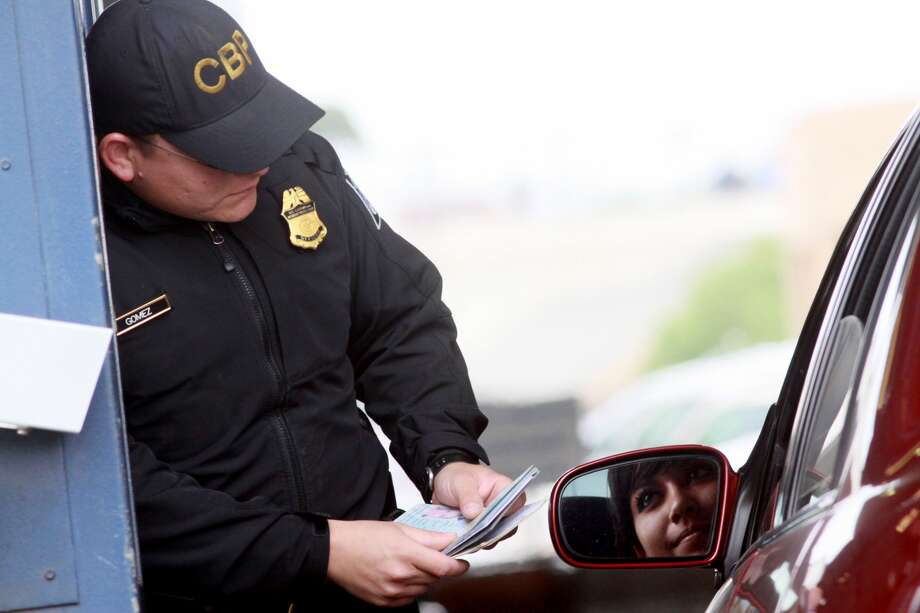 SAN YSIDRO, CA-, JUNE 1:  Customs and Border Protection agent Jesus Gomez checks a passport at the vehicle crossing at the San Ysidro Port of Entry June 1, 2009 in San Ysidro, California.  The Western Hemisphere Iniative (WHTI) was put into effect today at all Canadian and Mexican border crossings where visitors and residents must present an approved travel document when entering the U.S. at any land or sea ports of entry. These travel documents include a U.S. passport or passport card, as well as a Trusted Traveler Card (SENTRI, NEXUS or FAST) or an Enhanced Driver's License.  (Photo by Sandy Huffaker/Getty Images) Photo: Sandy Huffaker/Getty Images