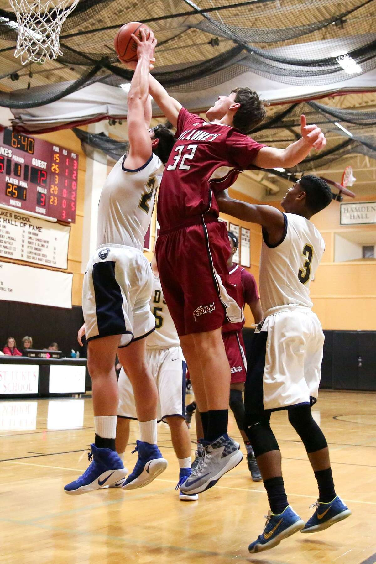 St. Luke's Porter Bowman and Rye Country Day School's Doug Kosann leap for the rebound during St. Luke's victory over the Wildcats in New Canaan, Conn. on Tuesday, Feb. 14, 2107.