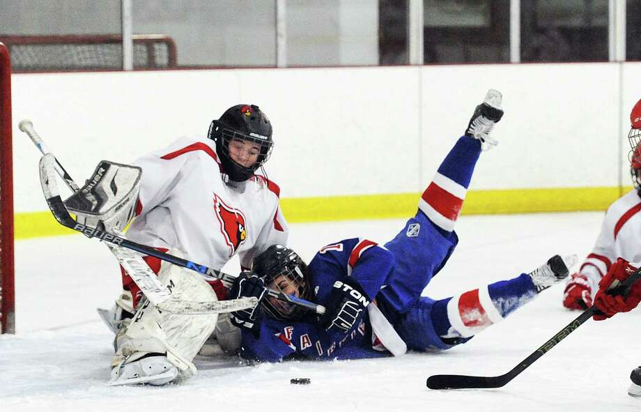 Fairfield Ludlowe/Warde's Sarah Powlishen (16), right, who was taken down on a penalty by Emily Bello of Greenwich (not in photo), crashes into Greenwich goalie Jessica Ware who still is able to make a stop on the puck during the girls high school ice hockey match between Greenwich High School and Fairfield Ludlowe/Warde Combined at Hamill Rink in Greenwich, Conn., Tuesday, Feb. 14, 2017. Photo: Bob Luckey Jr. / Hearst Connecticut Media / Greenwich Time