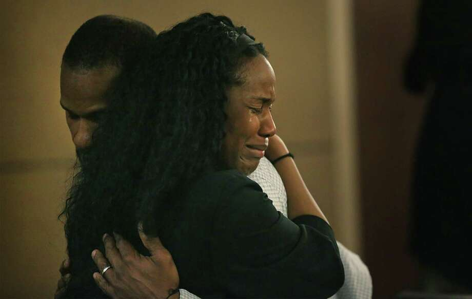 Qwalion Busby, left, charged with injury to a child by omission in regard to his son, who died after a severe infection in 2015, is embraced by a grieving family member after hearing the guilty verdict read in the Cadena-Reeves Justice Center, on Tuesday, Feb. 14, 2017. Busby and his wife Marquita Johnson were found guilty. Photo: Bob Owen /San Antonio Express-News / ©2017 San Antonio Express-News