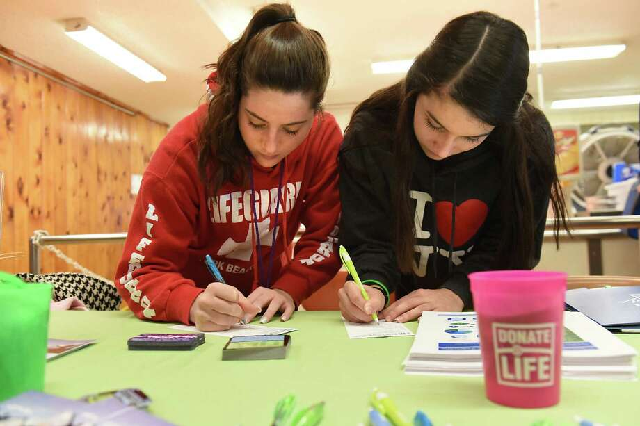 Senior students Jenny Picarillo, 17, left, and Ava Sweeney, 17, fill out donor forms during a young adult organ, eye and tissue registry drive at Catholic Central High School on Tuesday, Feb. 14, 2017 in Troy, N.Y. Jenny's mother received a kidney transplant and Ava's grandmother received a double lung transplant. The two girls organized the drive. (Lori Van Buren / Times Union) Photo: Lori Van Buren / 20039697A