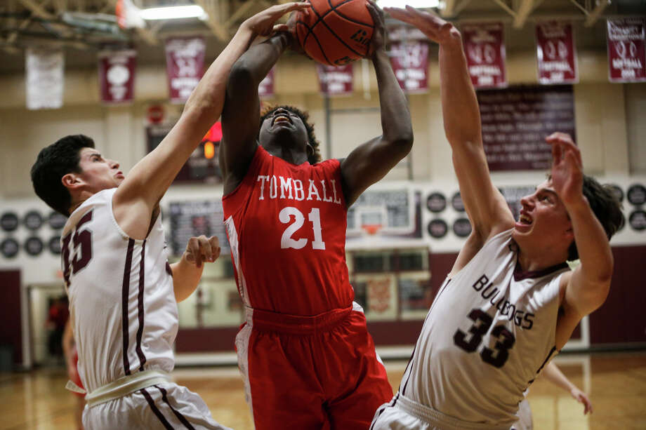 Tomball's Donald Doakes (21) shoots as Magnolia's Adam Kloffenstein (45) and Jackson Moffatt (33) defend during the varsity boys basketball game on Tuesday, Feb. 14, 2017, at Magnolia High School. (Michael Minasi / Chronicle) Photo: Michael Minasi, Staff Photographer / © 2017 Houston Chronicle