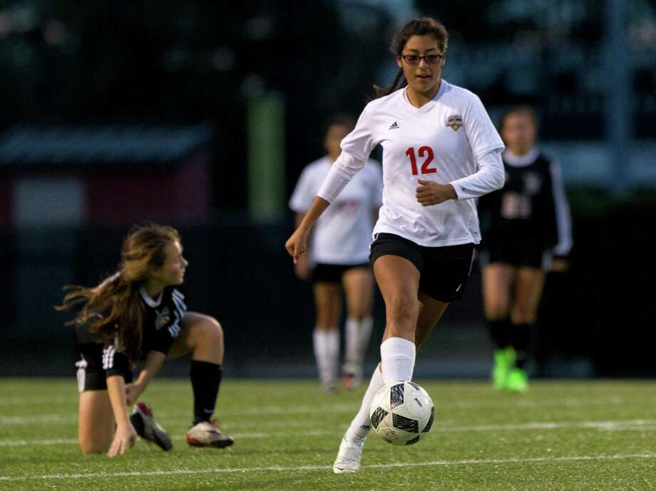 Caney Creek's Emily Carrisales (12) dribbles past Porter's Atliy Kolodziejski (15) during the second period of a District 21-5A high school girls soccer match at Buddy Moorhead Stadium Tuesday, Feb. 14, 2017, in Conroe. Photo: Jason Fochtman, Staff Photographer / © 2017 Houston Chronicle