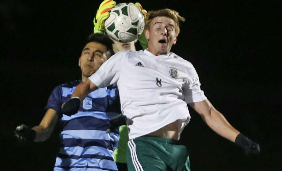 Reagan's Justin Sukow (right) is unable to score as Johnson goalkeeper Andrew Mcllvoy intercepts the ball during a District 26-6A high school soccer game on Feb. 14, 2017. Photo: Ron Cortes /For The Express-News / Freelance