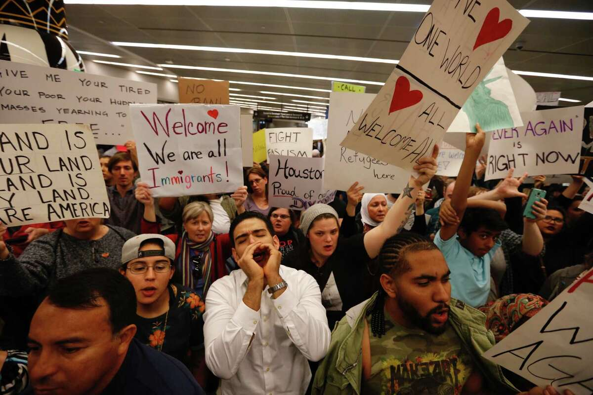 Demonstrators protest President Donald Trump's immigration policies and travel ban at the international arrivals area at Bush Intercontinental Airport.