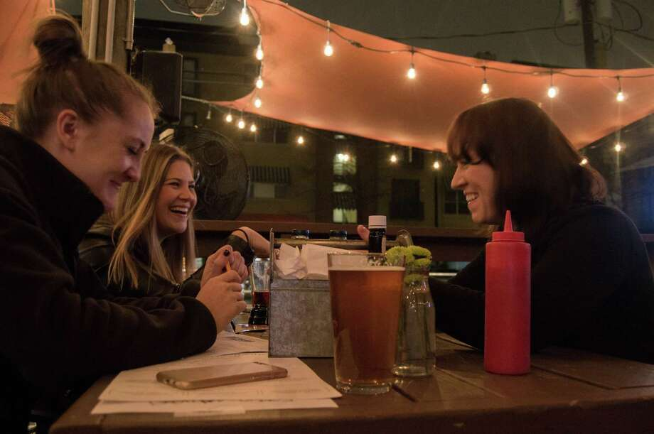 Jamie Simon (far left), Cassi Cruser (left) and Shawn Yates (right) share a laugh over one of the questions. Front Porch Pub hosted a Battle of the Sexes game night to celebrate a cold Valentines day. Contestants enjoyed beer, steaks and a surge of questions centered on pop culture and sexual trivia. Photo: Ajani Stewart / Houston Chronicle