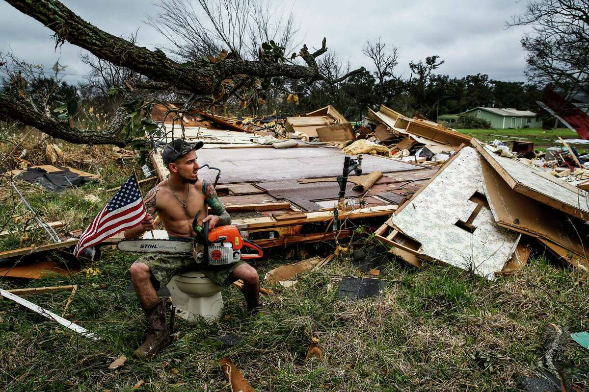 Hunter Brown poses for a photo with an american flag and a chainsaw while sitting on a toilet from a trailer that was destroyed when a tornado came through the area early Tuesday, Feb. 14, 2017 in Van Vleck.