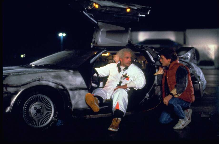 """This photo provided by Universal Pictures Home Entertainment shows Christopher Lloyd, left, as Dr. Emmett Brown, and Michael J. Fox as Marty McFly in the 1985 film, """"Back to the Future."""" Wednesday's so-called """"Back to the Future"""" Day marks the date - Oct. 21, 2015 - that characters McFly, Brown and Jennifer Parker famously journeyed to the future in the film trilogy's second installment in 1989. """"The Back to the Future 30th Anniversary Trilogy"""" and """"Back to the Future: The Complete Adventures"""" release on Blu-ray and DVD on Oct. 20. (Universal Pictures Home Entertainment via AP) ORG XMIT: CAET645 ORG XMIT: MER2015102021384177 / Universal Pictures Home Entertai"""