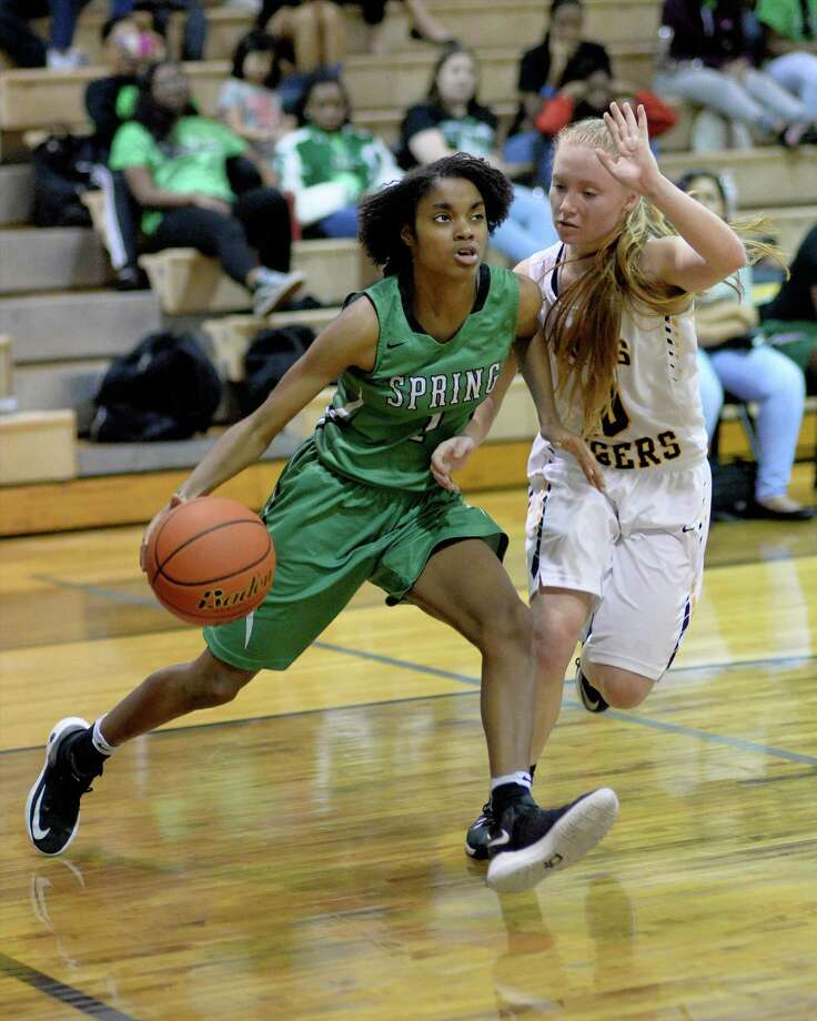 Kaitlyn Davis (1) of Spring makes a baseline drive past Addison Jacobs (10) of Spring Woods during the second half of the girls Bi-District playoff game between the Spring Woods Tigers and the Spring Lions on Tuesday February 14, 2017 at Spring Woods High School, Houston, TX. Photo: Craig Moseley, Staff / ©2016 Houston Chronicle