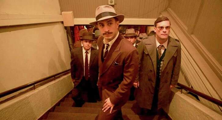 """Gael García Bernal, center, stars as a police inspector hot on the trail of renegade Chilean senator and poet Pablo Neruda in """"Neruda,"""" screening Saturday at 14 Pews."""