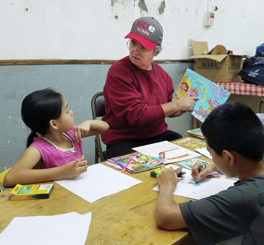 SIUE Chancellor Dr. Randy Pembrook reads to a small group of children during his service trip to Costa Rica. Photo: SIUE Photo