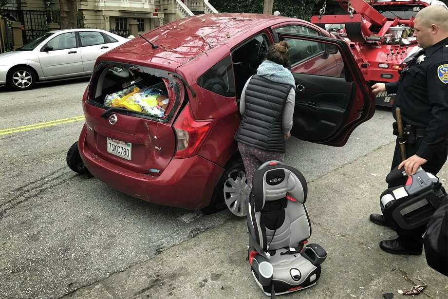Laura Espino, 32, removes a car seat from her Nissa Versa that was struck overnight when a driver crashed after being shot and killed. Photo: Evan Sernoffsky / The Chronicle / /