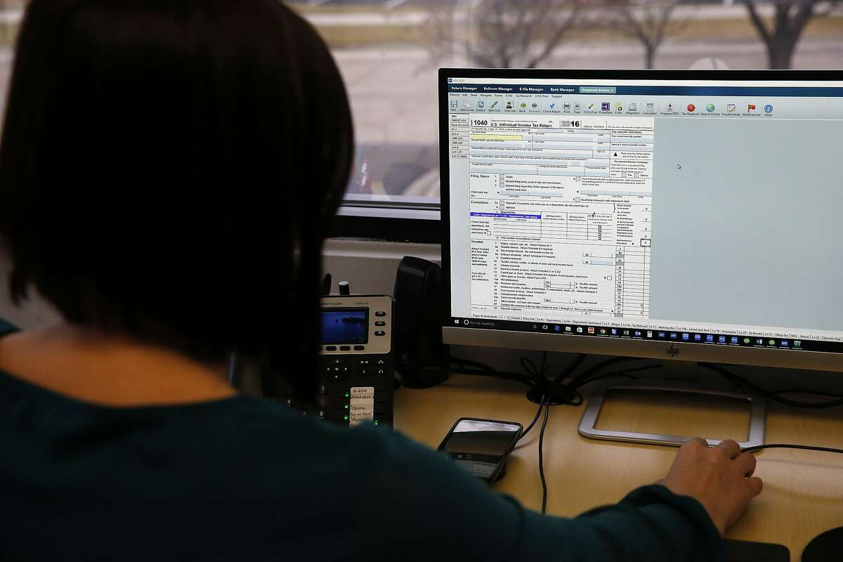 In this Jan. 14, 2017, photo, tax professional and tax preparation firm owner Alicia Utley views a Form 1040 on her computer in her office at Infinite Tax Solutions, in Boulder, Colo. Millions of Americans are eligible for Earned Income Tax Credit but many overlook its generous benefits. A tax preparer and most major tax software can walk you through a series of questions to determine your eligibility. (AP Photo/Brennan Linsley)