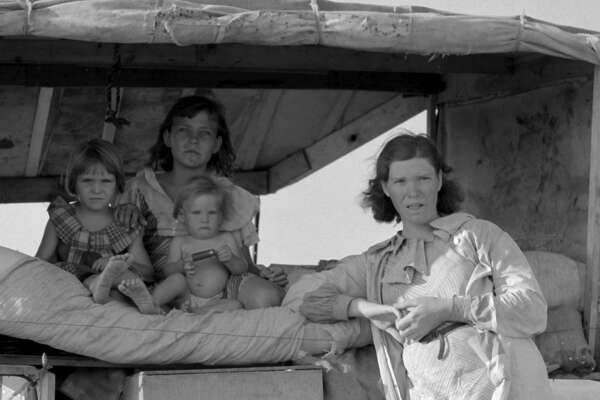 "UNITED STATES - CIRCA 1936:  Family between Dallas and Austin, Texas. The people have left their home and connections in South Texas, and hope to reach the Arkansas Delta for work in the cotton fields. Penniless people. No food and three gallons of gas in the tank. The father is trying to repair a tire. Three children. Father says, ""It's tough but life's tough anyway you take it""  (Photo by Buyenlarge/Getty Images)"