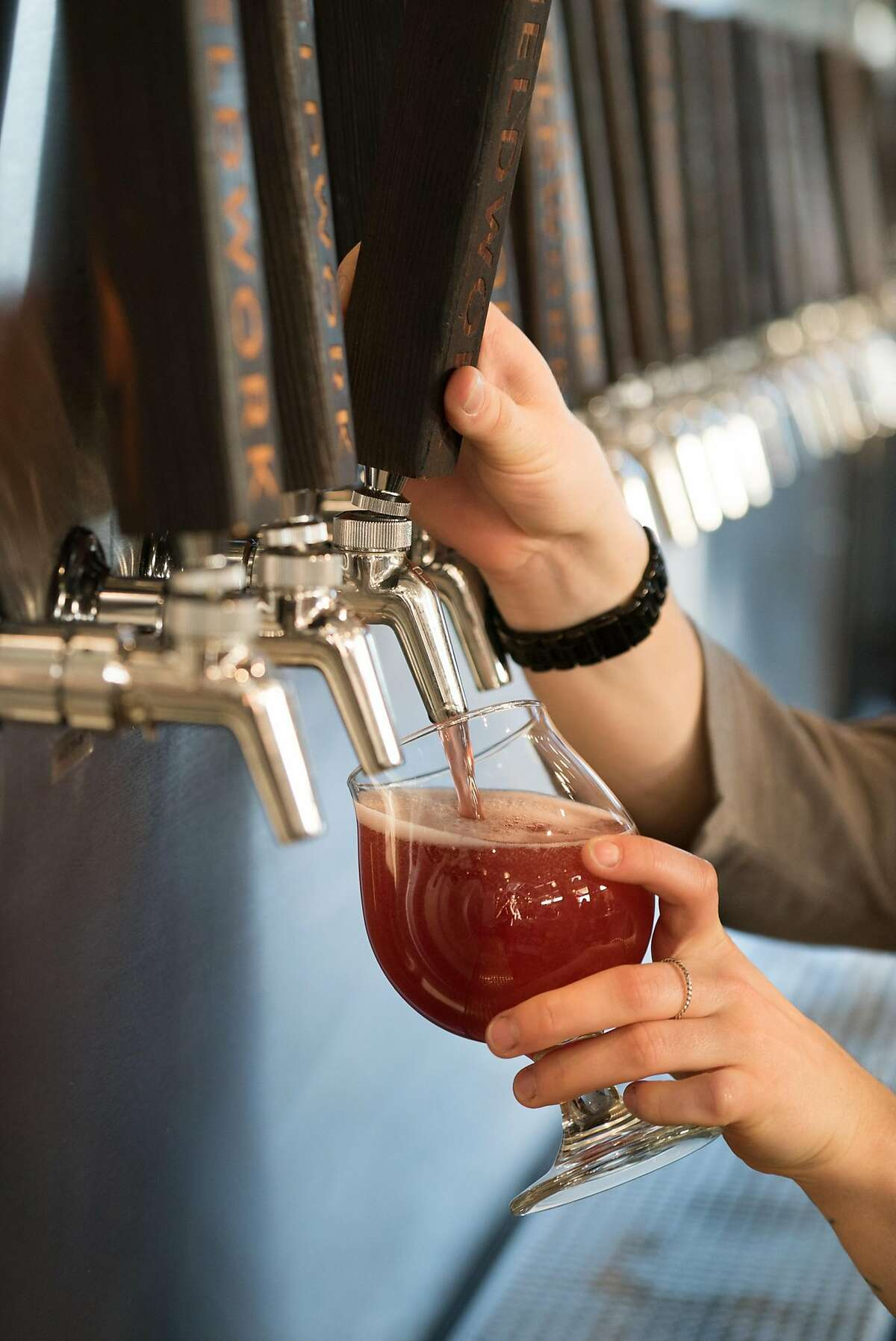 Curstin Perry pours a beer for a customer at Fieldwork inside the Oxbow Market in Napa, Calif. on Saturday, Feb. 11, 2017. Fieldwork features a variety of craft beers on tap.