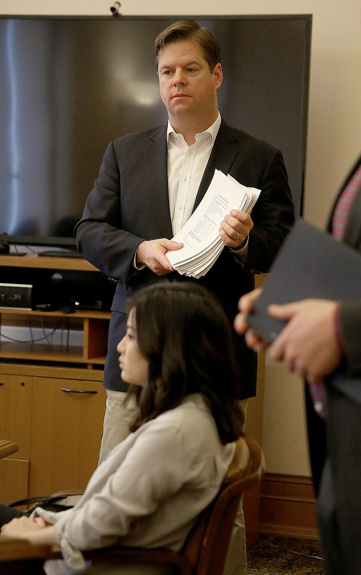 San Francisco supervisor Mark Farrell hands out surveys as he holds a community group meeting to discuss getting the city of San Francisco access to high speed internet at city hall on Tuesday, February 14, 2017, in San Francisco, Calif.