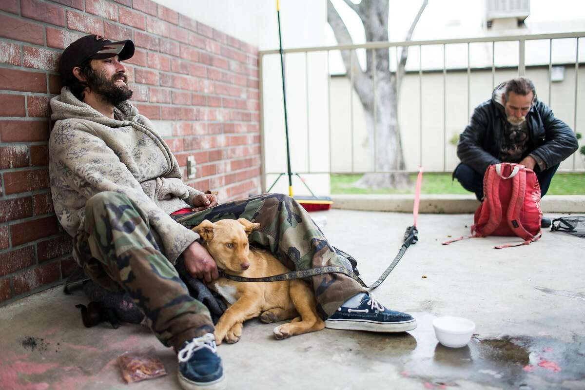 Matt Perry, left, who lives homeless in Oroville, continues to stay at the evacuation center at the Butte County Fairgrounds, with his dog, Honey, in Chico, California on February 15, 2017.