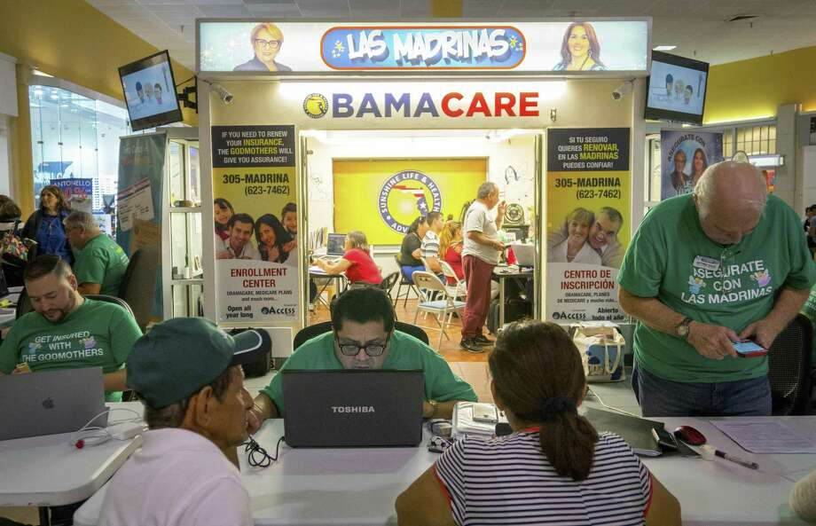 Insurance agent Rudy Figueroa (center) checks information on his computer while helping customers at the Sunshine Health and Life Advisors kiosk inside the Mall of the Americas in November in Miami. Photo: Angel Valentin /New York Times / NYTNS