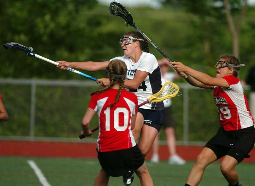 Wilton's Casey Pearsall shoots and scores as New Canaan's Sarah Mannelly, left, and Hannah Femia defend during the Girls Lacrosse FCIAC Championship game Friday May 28, 2010 at Brien McMahon High School in Norwalk.