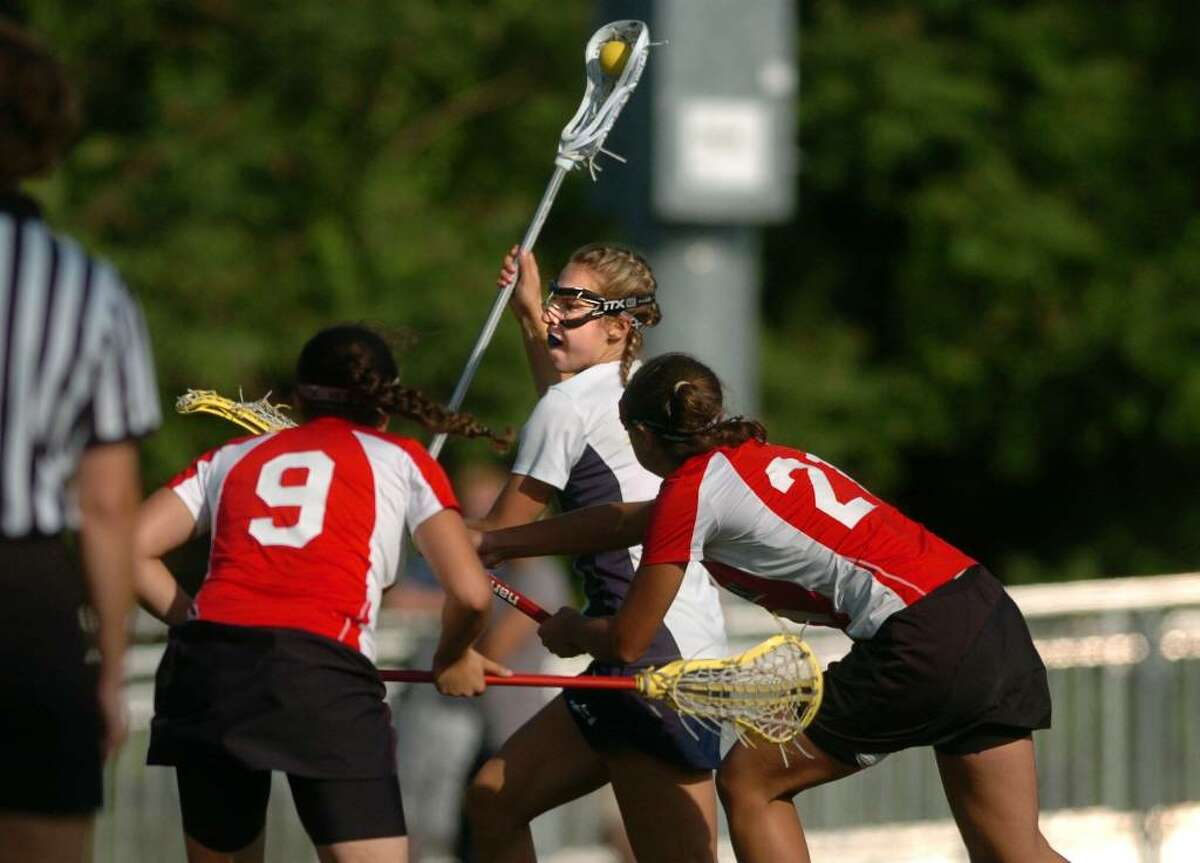 Wilton's Tessa Howard weaves between New Canaan's Lauren Freeland, left, and Erin Fessler on her way to a goal during the Girls Lacrosse FCIAC Championship game Friday May 28, 2010 at Brien McMahon High School in Norwalk.