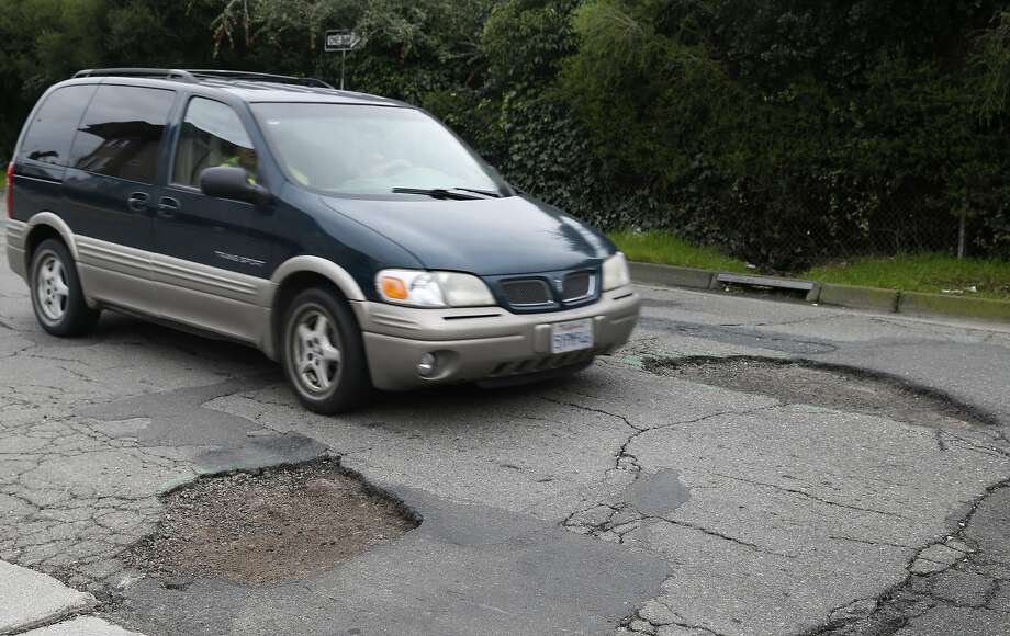 A driver slows down to pass between two large potholes on Chatham Road in Oakland, where street maintenance crews are struggling to keep up after constant rain. Photo: Paul Chinn, The Chronicle
