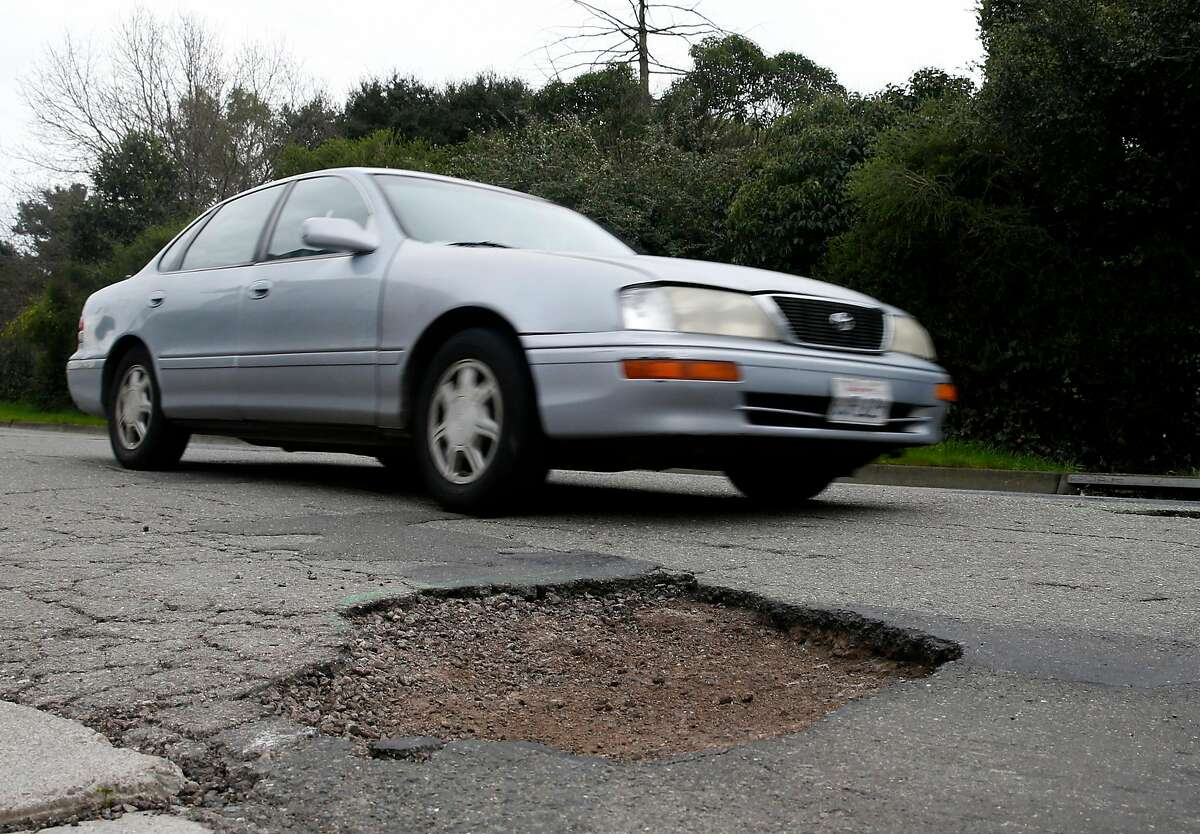 FILE-- A commuter slows down to drive past large potholes on Chatham Road in Oakland, Calif. on Wednesday, Feb. 15, 2017.Roads throughout the Bay Area are slowly improving, according to a new report, and officials at the Metropolitan Transportation Commission are crediting an infusion of SB1 gas tax dollars for the gradual upward trend.
