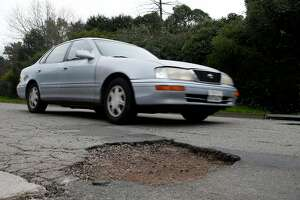 A commuter slows down to drive past large potholes on Chatham Road in Oakland, Calif. on Wednesday, Feb. 15, 2017. Street maintenance crews are struggling to keep up with a large number of potholes due to the constant rain.