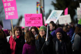 Both pro-choice and pro-life protesters gathered outside a Planned Parenthood to counteract one another in Kent, Wash. on Saturday, Feb. 11, 2017. Pro-choice demonstrators marched in and outnumbered the defund Planned Parenthood demonstrators.