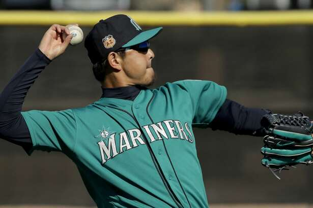 Seattle Mariners pitcher Hisashi Iwakuma throws during spring training baseball practice, Wednesday, Feb. 15, 2017, in Peoria, Ariz. (AP Photo/Charlie Riedel)