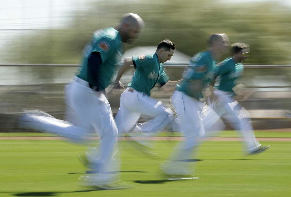 Seattle Mariners players run sprints during spring training baseball practice Wednesday, Feb. 15, 2017, in Peoria, Ariz. (AP Photo/Charlie Riedel)