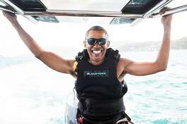 In a recent handout picture released by Virgin on February 7, 2017, former US president Barack Obama is pictured during a kitesurfing session with British billionaire Richard Branson, off the coast of Moskito Island in the British Virgin Islands in the Caribbean. / AFP PHOTO / Hijack.life/Virgin.com / JACK BROCKWAYJACK BROCKWAY/AFP/Getty Images