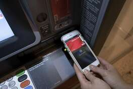 A customer uses her smartphone and an ATM to do banking transactions, at the Bank of America Tower in Manhattan, Jan. 27, 2017. Major banks are already testing -- and will soon offer more widely -- teller machines that give you access with your phone, dispensing with the need for an ATM card. But the feature raises new security issues. (James Estrin/The New York Times)