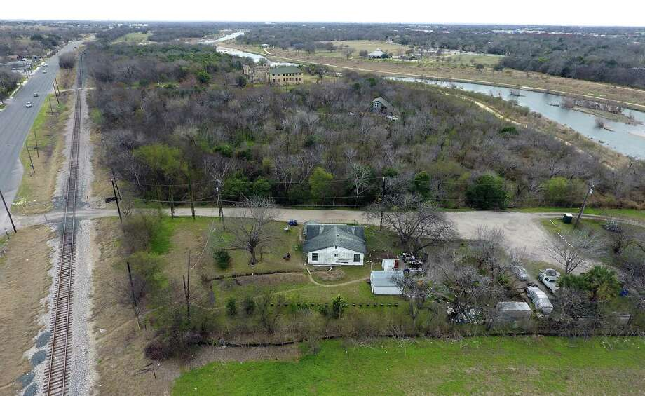 The Hot Well resort ruins can barely be seen Thursday, Feb. 2, 2017 surrounded by trees in the background of this aerial image taken with a remote control quadcopter. The Torres family's property can be seen in the foreground with multiple homes and several buildings on it. Multiple members of the Torres family live on the small section of property that abuts the San Antonio River and the former Hot Wells resort property. The Torres family, who say they have owned their homestead on the river for 150 years are in a battle with Hot Wells property owner James Lifshutz. Lifshutz needs the Torres' land for road access to a development he plans to build on the Hot Wells property. The Torres family says Lifshutz has made them several offers for their land over the last 20 years, but they don't want to move. Now that Lifshutz and the county have a deal to turn the Hot Wells ruins into a park, the Torres family has received letters from the county that seem to suggest it might be considering using eminent domain against them. Photo: William Luther, Staff / San Antonio Express-News / © 2017 San Antonio Express-News