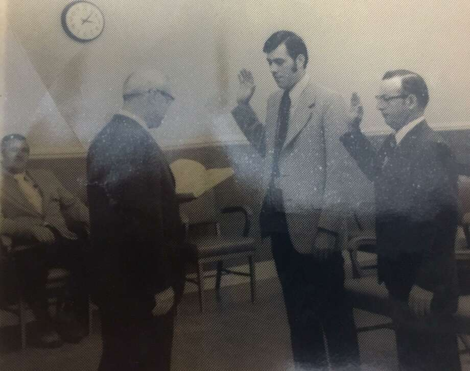 New Milford First Selectman Louis C. White, who died Feb. 8 looks on at left as Selectmen Clifford C. Chapin, right, and Terry Pellegrini, second from right, are sworn in by a gentleman believed to be Town Clerk Richard Gebhardt in 1973 at the start of White's second of three two-year terms. Photo: Courtesy Of Terry Pellegrini / The News-Times Contributed