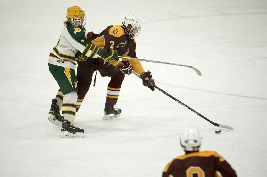 BRITTNEY LOHMILLER | blohmiller@mdn.net Davison High's Jourdan Schmidt works to control the puck while being defended by Dow High's Alec Newton in the first period of the Wednesday evening game. Photo: Brittney Lohmiller/Midland Daily News/Brittney Lohmiller