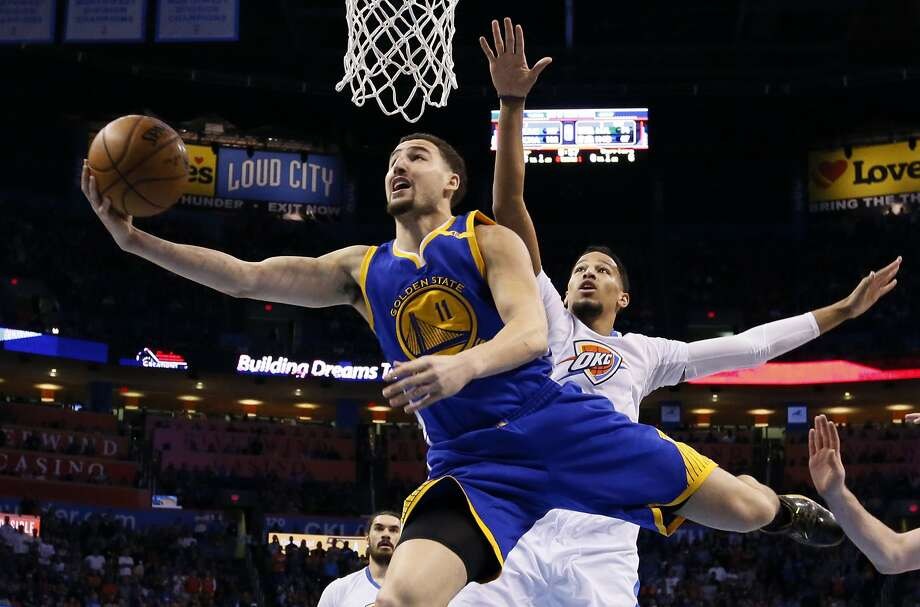 Golden State Warriors guard Klay Thompson (11) shoots in front of Oklahoma City Thunder forward Andre Roberson, right, in the first quarter of an NBA basketball game in Oklahoma City, Saturday, Feb. 11, 2017. (AP Photo/Sue Ogrocki) Photo: Sue Ogrocki, Associated Press