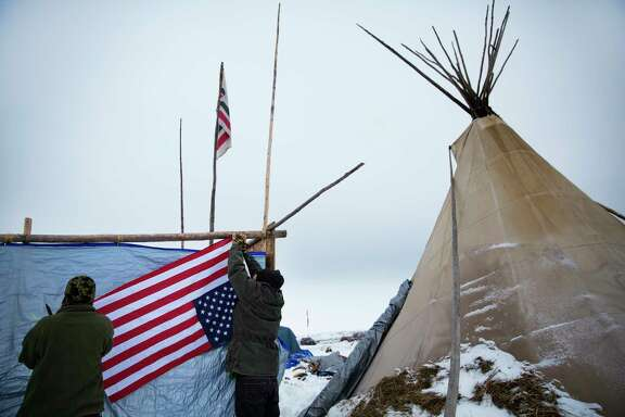 Arapaho tribal members  hang a flag upside down at the Oceti Sakowin camp in Cannon Ball, N.D.