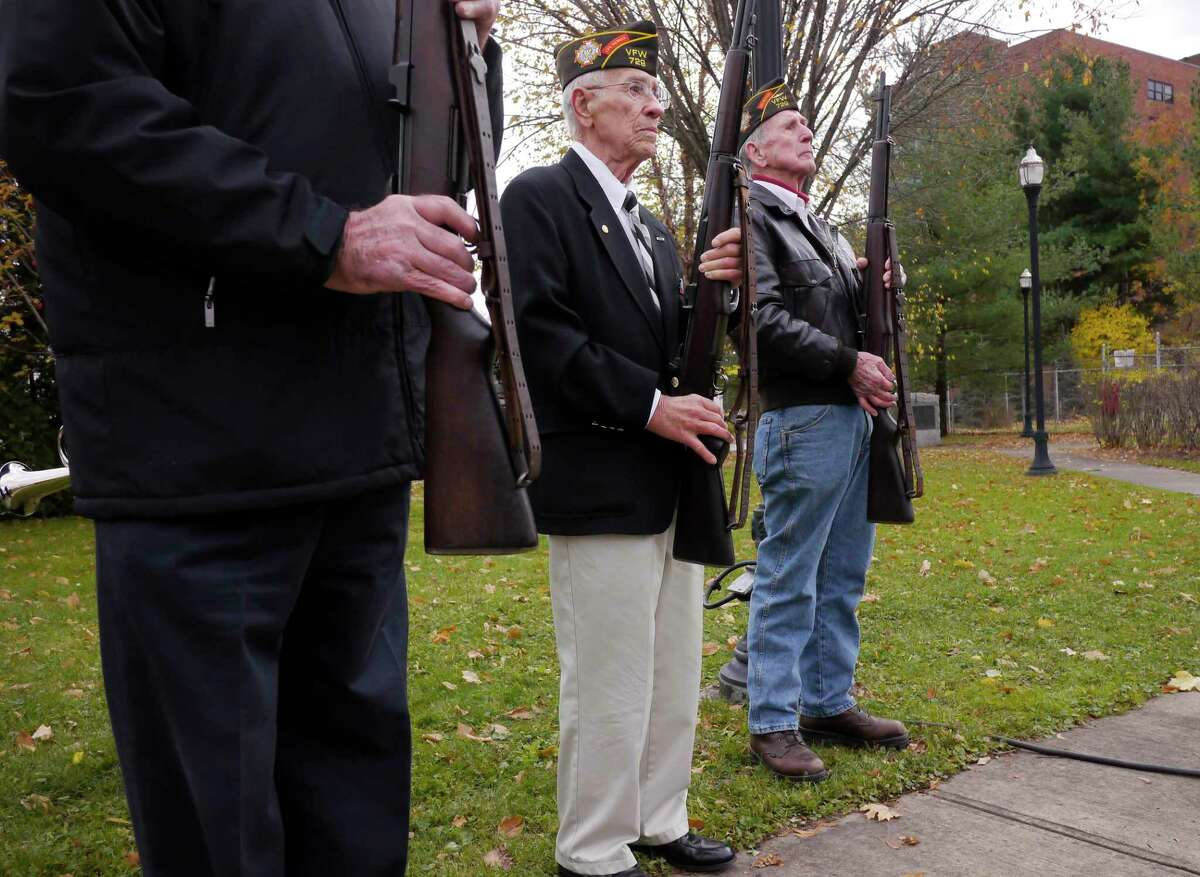 Watervliet VFW Post 729 members, Bill Millette, left, who served in the Army, Robert Gusberti, center, who served in the Navy, and Stan Hatter, who served in the Air Force, stand ready to give a rifle salute during a Veterans Day ceremony at Veterans Memorial Park on Monday, Nov. 11, 2013 in Watervliet, NY. (Paul Buckowski / Times Union)
