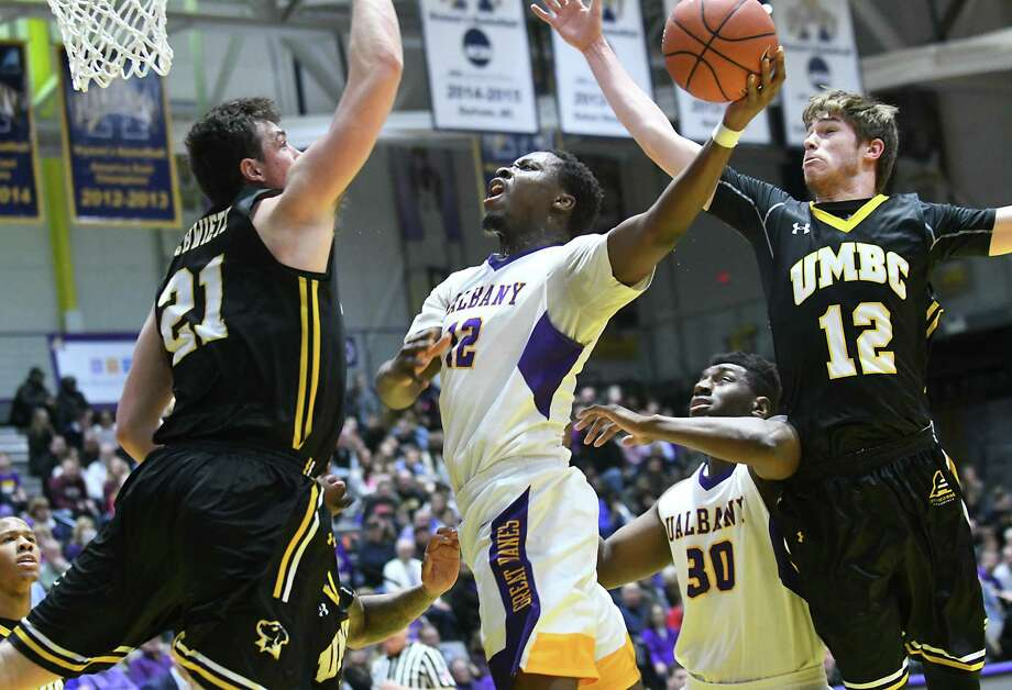 University at Albany's Devonte Campbell is fouled as he is defended by UMBC's Sam Schwietz, left, and Will Darley during a basketball game at the SEFCU Arena on Wednesday, Feb. 15, 2017 in Albany, N.Y. (Lori Van Buren / Times Union) Photo: Lori Van Buren / 20039507A