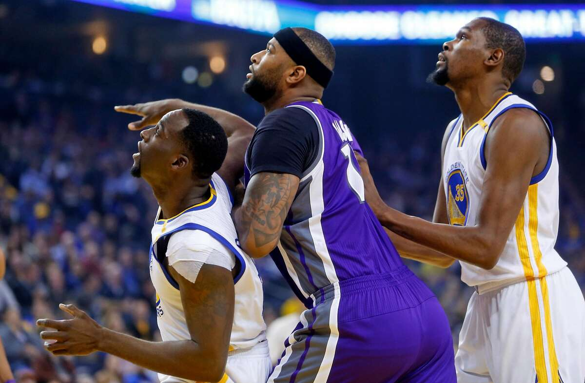 Golden State Warriors' Draymond Green and Kevin Durant box out Sacramento Kings' DeMarcus Cousins in 1st quarter during NBA game at Oracle Arena in Oakalnd, Calif., on Wednesday, February 15, 2017.