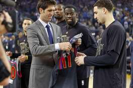 Golden State Warriors' Bob Myers gives Klay Thompson his All-Star Game jersey after Draymond Green, Kevin Durant and Stephen Curry received their jerseys before NBA game against Sacramento Kings at Oracle Arena in Oakalnd, Calif., on Wednesday, February 15, 2017.