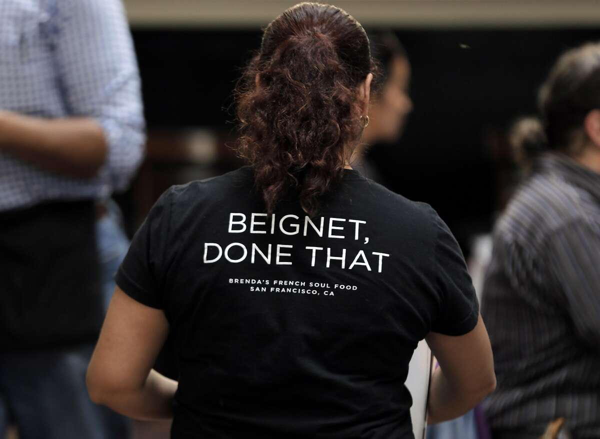 Server Maria Avelasco walks through the dining room wearing a staff shirt with the saying,