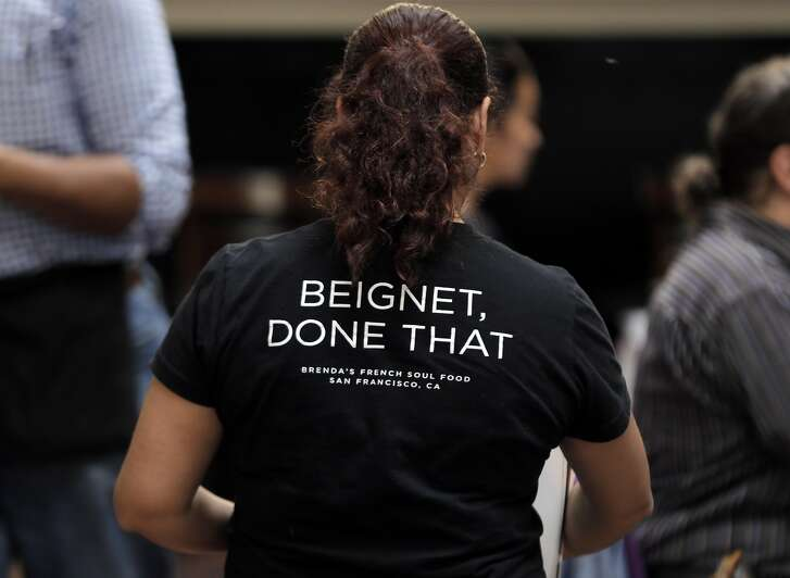 """Server Maria Avelasco walks through the dining room wearing a staff shirt with the saying, """"Beignet, Done That,"""" at Brenda's French Soul Food Restaurant in San Francisco, Calif., on Wednesday, February 15, 2017."""