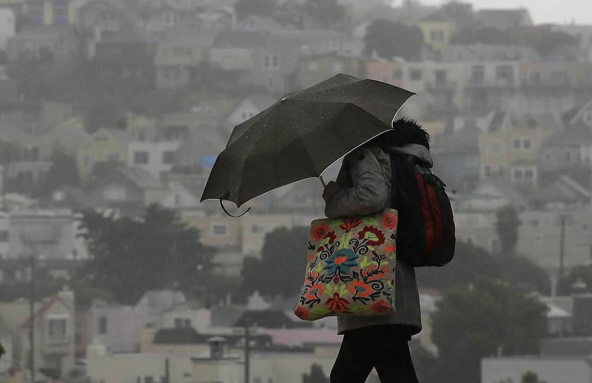 A woman carries an umbrella as she crosses a street in San Francisco, Tuesday, Feb. 7, 2017. Flash flood watches are in place for parts of Northern California down through the Central Coast as heavy rains swamp roads and threaten to overtop rivers and creeks. (AP Photo/Jeff Chiu)