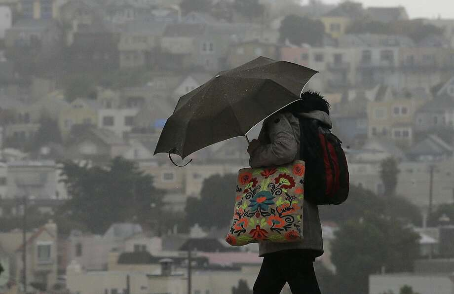 A woman carries an umbrella as she crosses a street in San Francisco, Tuesday, Feb. 7, 2017. The first in a series of rainstorms slammed the Bay Area Thursday morning, triggering car crashes across the region. Photo: Jeff Chiu, Associated Press