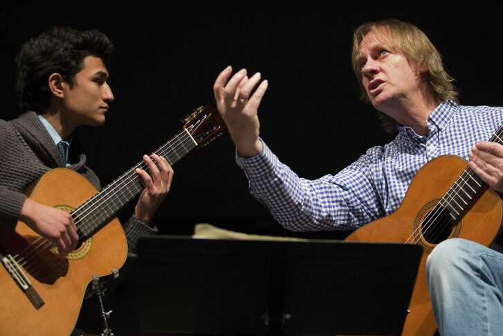 Abram Fernandez, a sophomore at USTA, gets a lesson from classical guitarist David Russell during Russell's master class at UTSA's downtown campus.