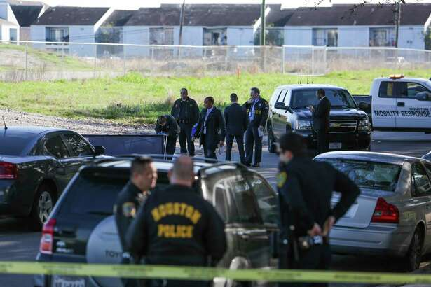 Houston homicide investigators search the area around a body that was found in the middle of Sharpcrest Street near the Sam Houston Tollway Thursday, Feb. 16, 2017 in Houston.